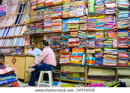 DELHI - DECEMBER 2: Two textile merchants sit in a wholesale shop stacked with fabric on shelves on December 2, 2007 in Delhi, India. Textiles exports may touch $24 billion in 2010-11 - stock photo