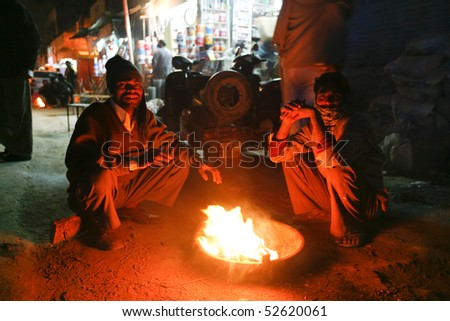 DELHI - FEBRUARY 11: Men sitting around street fire at night on February 11, 2008 in Delhi, India. Winters can get quite cold in the desert capital. - stock photo