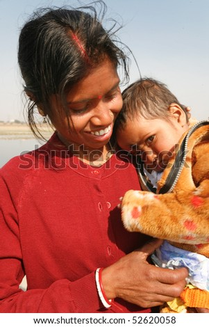 DELHI - FEBRUARY 14:  Outdoor portrait of mother carrying small child on February 14, 2008 in Delhi, India. - stock photo