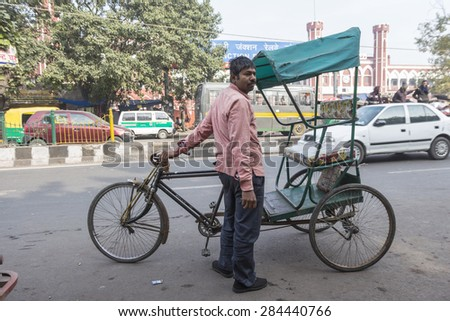 DELHI INDIA - DEC 20 :  rickshaw driver looking for passengers near old delhi railway station. this area is in old delhi, that is famous place of Delhi on december, 20, 2014, india - stock photo