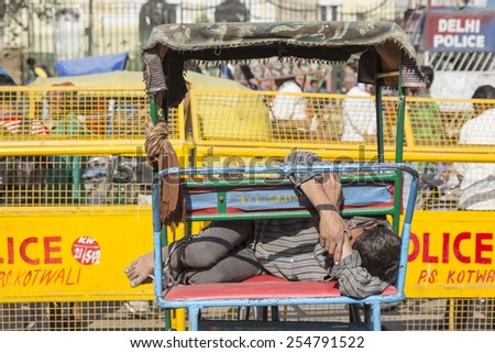 DELHI INDIA-DEC 10 : rickshaw driver sleep in his three-wheeler in chandni chowk. his job is hardship and most competition. rickshaw is hindu name of three-wheeler bike on december, 10, 2014, india - stock photo