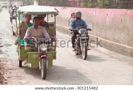 DELHI, INDIA - FEBRUARY 18, 2015: people ride different transport in some poor district of Delhi, India - stock photo