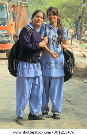 DELHI, INDIA - FEBRUARY 18, 2015: two girls in school clothes smile to someone in Delhi, India - stock photo