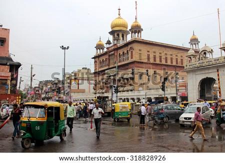DELHI, INDIA - JULY 20, 2015: People traveling around flower market near Shri Gauri Shankar Mandir. Traffic in Delhi at morning, India. JULY 20 2015 - stock photo