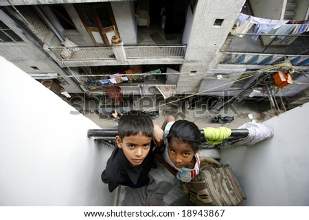 Delhi, India - May 2008. Social Issue. Two young school kids on balcony in Old Delhi before going to government school. - stock photo