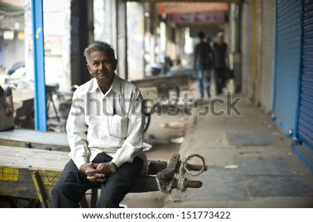 DELHI, INDIA - NOV 18: Unidentified old man chills out in a classical street in Old Delhi. November 18, 2012 in Delhi, India. The lifestyle in old delhi is still well kept like that in 100 years ago. - stock photo