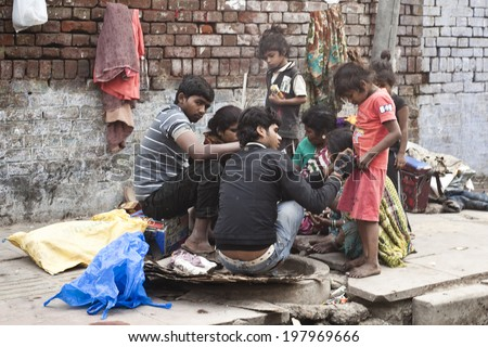 DELHI, INDIA - NOVEMBER 10: Morning on a street, poor indian family, at November 10, 2013 in Old Delhi, India. Indian capital still uses man powered rickshaws as a usual mean of transport.  - stock photo
