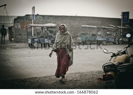 DELHI, INDIA - NOVEMBER 10: Morning on a street , poor woman with roti, at November 10, 2013 in Old Delhi, India.  - stock photo