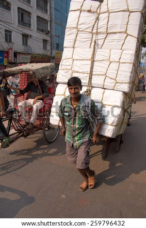 DELHI, INDIA - NOVEMBER 5: Unidentified man pulls cart with goods on November 5, 2014 in Delhi, India. As modern vehicles are too expensive hand-pulled carts are still in use in Delhi. - stock photo