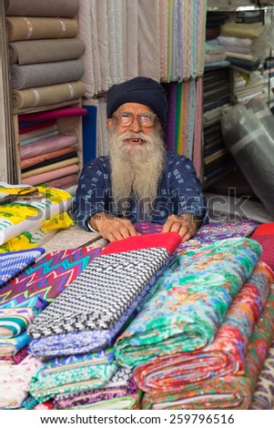 DELHI, INDIA - NOVEMBER 5: Unidentified man sells textile at Chandni Chowk on November 5, 2014 in Delhi, India. Chandni Chowk is one of the oldest and busiest markets in Old Delhi. - stock photo
