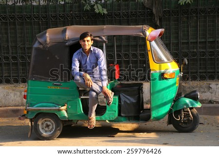 DELHI, INDIA - NOVEMBER 5: Unidentified man sits in his tuk-tuk on November 5, 2014 in Delhi, India. Autorickshaws are very popular means of public transportation in Delhi. - stock photo