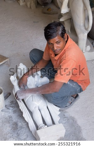 DELHI, INDIA - NOVEMBER 5: Unidentified man works  on a statue at a workshop on November 5, 2014 in Delhi, India. Delhi is the second most populous city in India. - stock photo