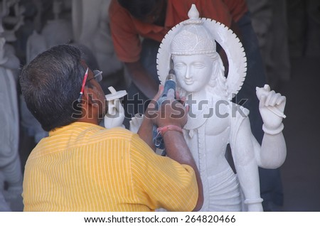 DELHI, INDIA - NOVEMBER 6: Unidentified man works on a statue at a workshop on November 6, 2014 in Delhi, India. Delhi is the second most populous city in India. - stock photo