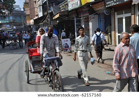 DELHI, INDIA - OCT 24: An unidentified indian woman travels by rickshaw in Delhi on October 24, 2009. Rickshaw men are one of the hardest working people and also poorest in the whole India. - stock photo