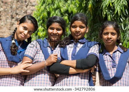 DELHI, INDIA - OCTOBER 11, 2015: unidentified local school girls for tour in Qutub Minar complex, Delhi, India, as part of national education. The girls in school uniform have fun posing for a foto.  - stock photo