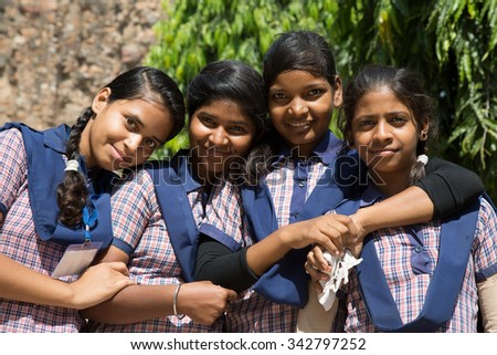 DELHI, INDIA - OCTOBER 11, 2015: unidentified local school girls for tour in Qutub Minar complex, Delhi, India, as part of national education. The girls in school uniform have fun posing for a photo.  - stock photo