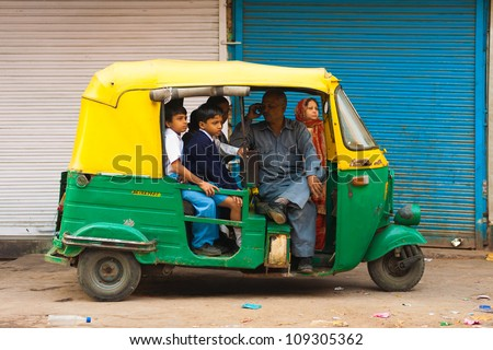 Delhi, India - October 27, 2009: Young children crammed into a private auto rickshaw waiting patiently to be transported to school while driver talks on mobile phone without any care in the world - stock photo