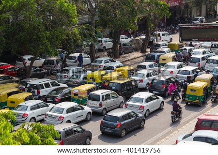 DELHI, INDIA - 19TH MARCH 2016: Large amounts of traffic on a road in India during the day. Tuk Tuk Rickshaws, motorbikes, cars and people can be seen. - stock photo