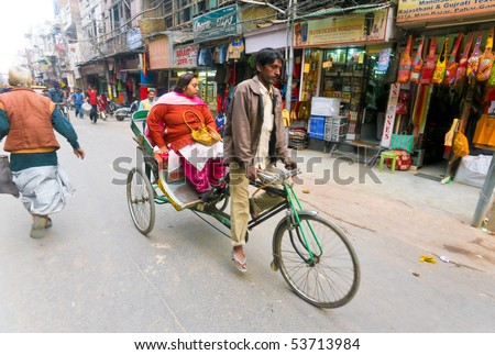 DELHI - JAN 15: Man driving female passenger on a cycle rickshaw through city area on January 15, 2008 in Delhi, India. This is the cheapest means of transport when you're in no rush. - stock photo