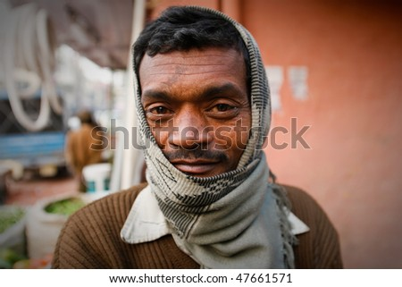 DELHI - JANUARY 31: Portrait of a day labourer January 31, 2008 in Delhi, India. These men sit on the street hoping to get day jobs not paid more than 2,5 dollars a day. - stock photo