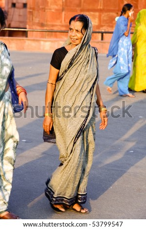 DELHI - SEP 22: Middle-aged woman on street wearing traditional sari  on September 22, 2007 in Delhi, India.  Saris are wrapped around the body, 4 to 8 metres in length. - stock photo
