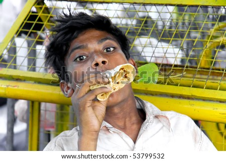 DELHI - SEP 22: Portrait of boy eating on street on September 22, 2007 in Delhi, India. UNHCHR has estimated that India has the largest population of street children in the world. - stock photo