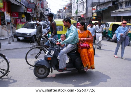 DELHI - SEPTEMBER 19: Mother, father and small child riding on scooter through busy city street on September 19, 2007 in Delhi, India. Up to six family members manage to ride these  two wheelers. - stock photo