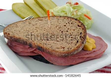 Deli sandwich served with pickles and coleslaw. - stock photo