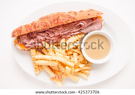deli style sliced rare roast beef on a cheese bun with french fries and gravy - stock photo