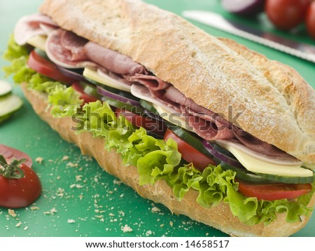 Deli Sub Sandwich on a Chopping Board - stock photo