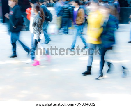 Deliberately blurred people walking action - stock photo