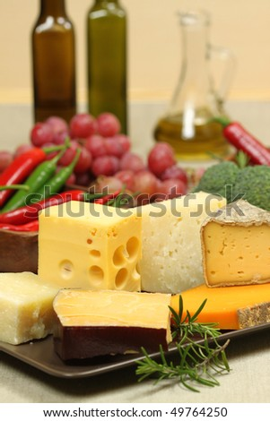 Delicacies. Food composition - hard and soft cheese varieties and vegetables.