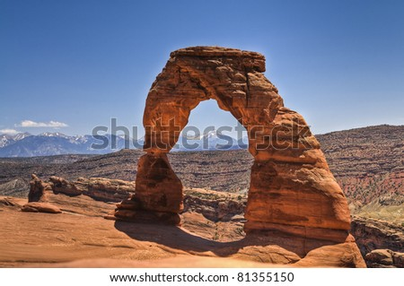 Delicate Arch with mountains in the background - stock photo