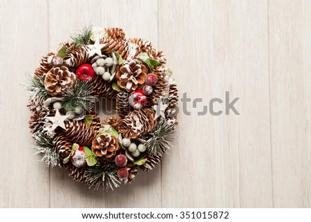Delicate Christmas wreath of pine cones on gray wooden background - stock photo