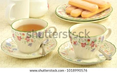 Delicate ladyfinger cookies with tea in pretty springtime china