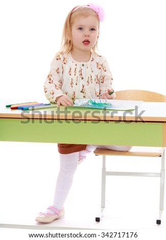 Delicate little blonde girl in yellow shorts and a bright shirt draws sitting at her Desk - Isolated on white background - stock photo