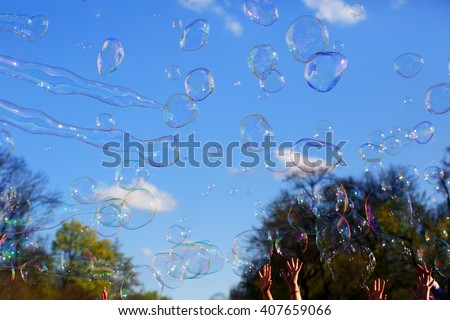 Delicate soap bubbles and kids hands in the park