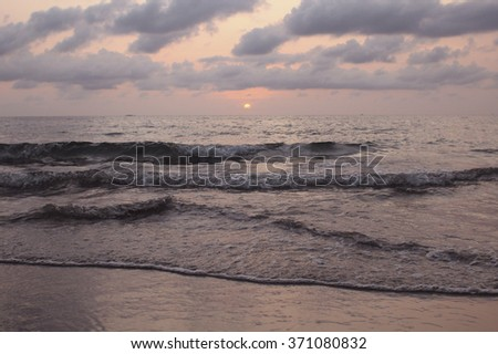 Delicate sunset on the island in the ocean. - stock photo