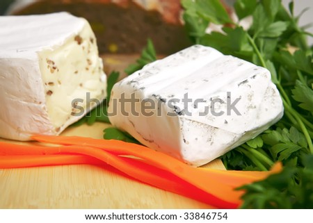 delicatessen cheese on cut board with bread and vegetables