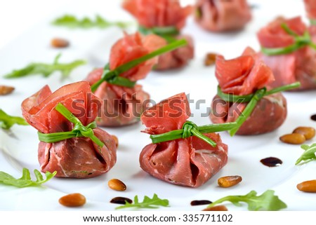 Delicious air-dried beef ham - Italian Bresaola -  stuffed with chopped rocked salad, roasted pine nuts, parmesan cheese and creamy balsamic vinegar, tied up with blanched chives  - stock photo