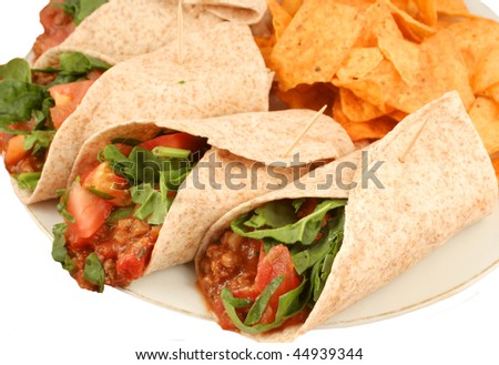 Delicious and colorful mexican fajitas or wraps, and crunchy nacho chips - stock photo