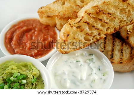 Delicious and colorful trio of dips with grilled Turkish bread. - stock photo