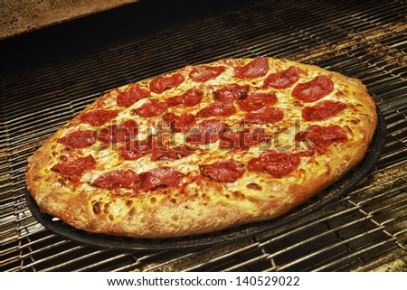 Delicious and fresh pepperoni pizza coming out of the oven. - stock photo