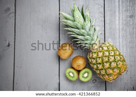 Delicious and healthy kiwi and pineapple fruit on grey wooden background - stock photo