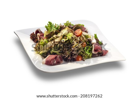 Delicious and healthy salad with lettuce, pears, bacon and tomatoes isolated on white - stock photo