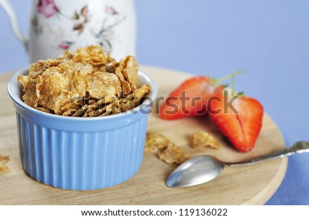 Delicious and nutritious bran flakes cereal in blue bowl with strawberry on wooden cutting board - stock photo