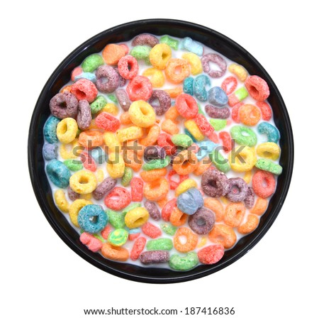 Delicious and nutritious fruit cereal loops flavorful in black bowl and milk on white background, healthy and funny addition to kids breakfast  - stock photo