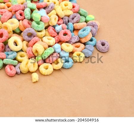 Delicious and nutritious fruit cereal loops flavorful on brown paper, healthy and funny addition to kids breakfast  - stock photo