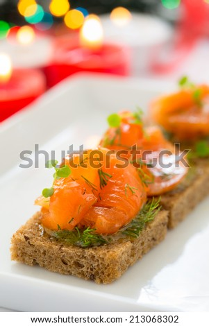 Delicious appetizer canapes of black bread with smoked salmon for holiday - stock photo