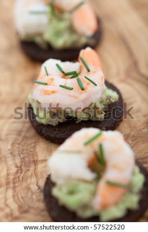 Delicious appetizer of prawns and guacamole on a pumpernickel rye bread. Shallow DOF - stock photo